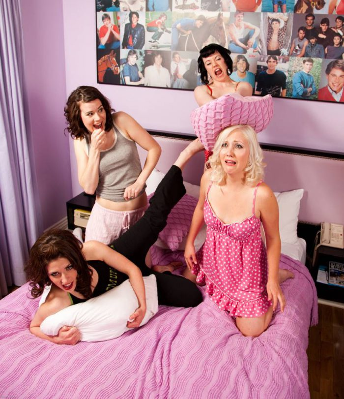 Artistic portrait of four women in a pillow fight.
