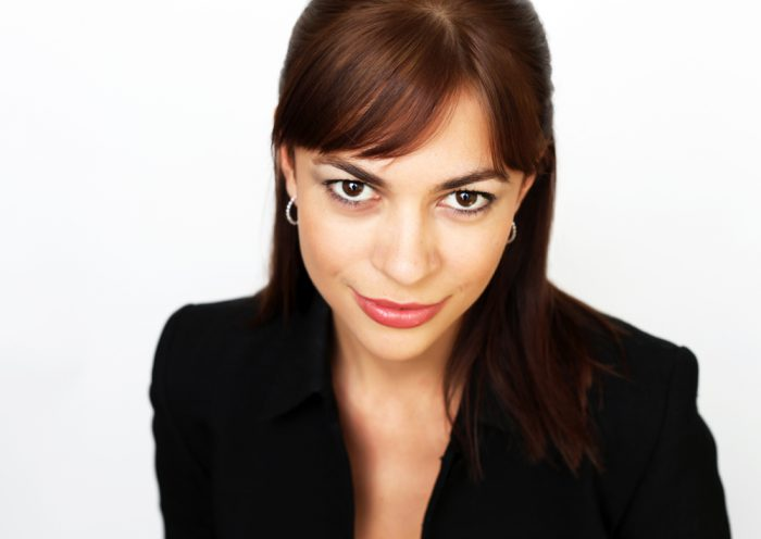 Professional corporate headshot of a woman on a white background.