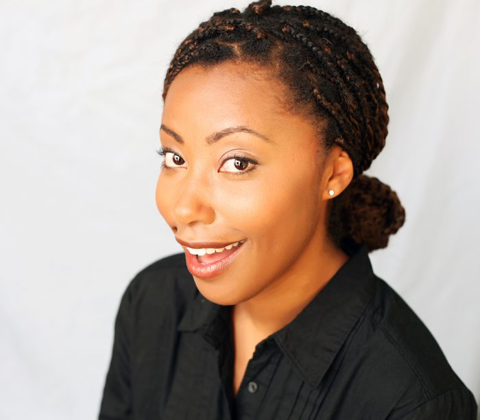 Professional headshot of a woman in black on a white background.