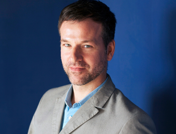 Corporate Portrait of a man in a blazer on a blue background.