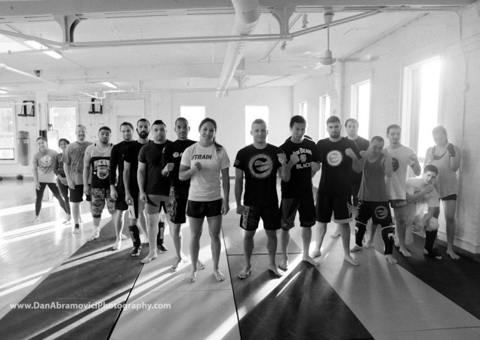 Artistic black and white portrait of a MMA fighter and her team.