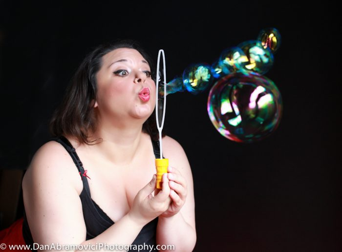 Artistic portrait of a woman blowing bubbles on a black background.