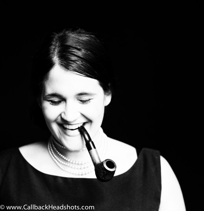 Artistic black and white portrait of a woman with a pipe on a black background.