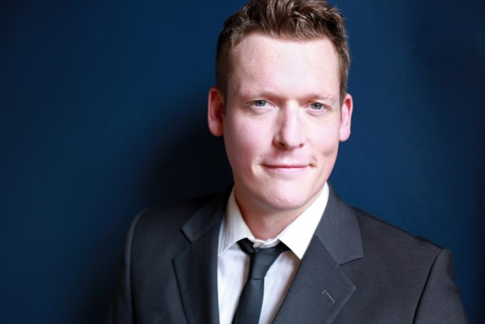 Professional headshot of an actor in a suit on a blue background.