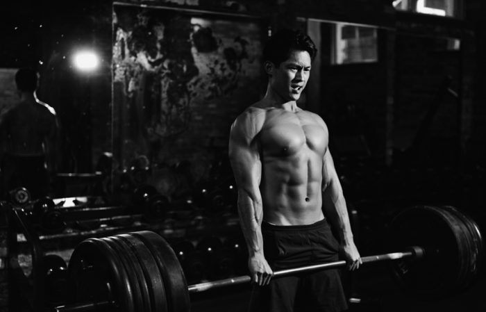 Artistic black and white photograph of a fitness trainer working out in his gym.