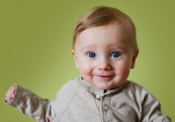 Professional portrait of a happy baby on a green background.