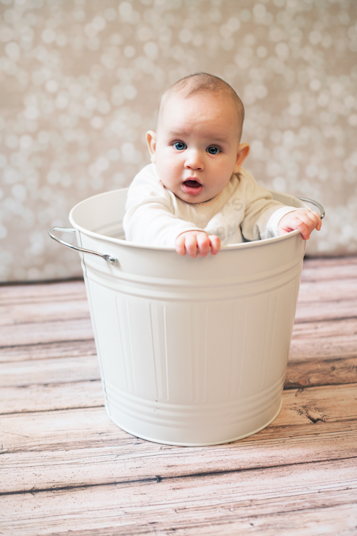 Artistic portrait of a baby hiding in a bucket.