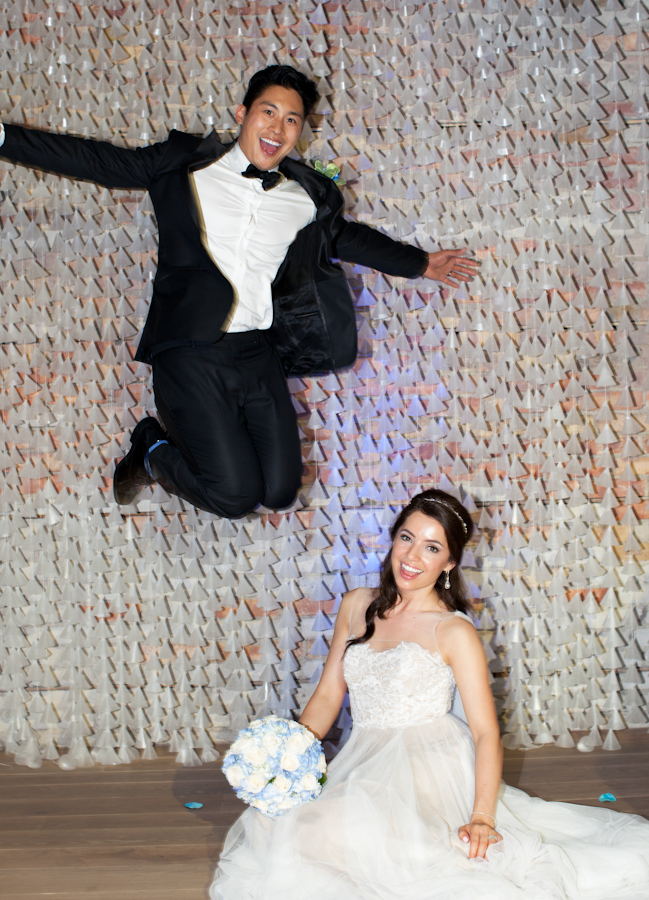 Artistic wedding photography of a man jumping over his new marriage.