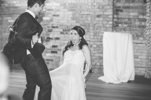 Artistic black and white wedding photograph of a groom dancing for his bride.