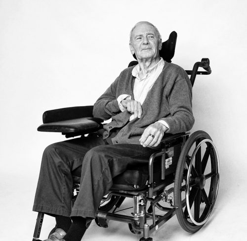 Artistic black and white portrait of a man in a wheelchair.