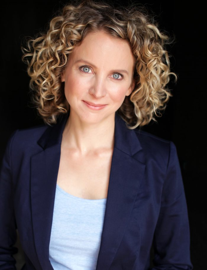 Professional corporate portrait of a woman in a blazer on a black background.