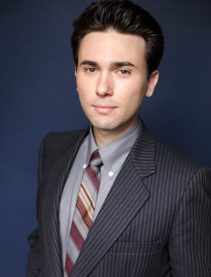 Professional portrait of a lawyer in a suit and tie against a blue background.
