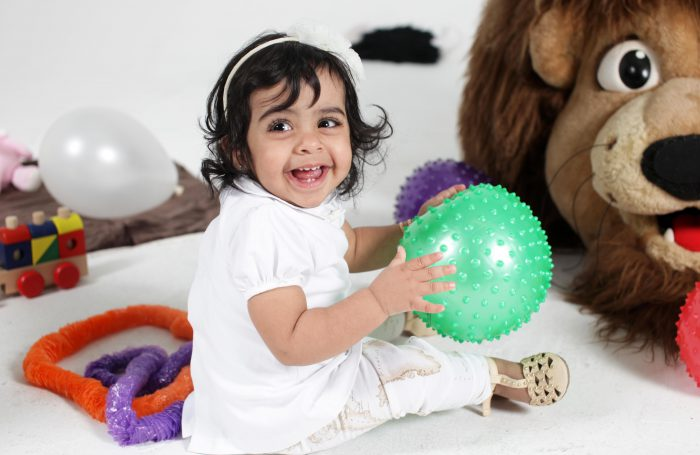 Beautiful portrait of a baby playing with a ball.