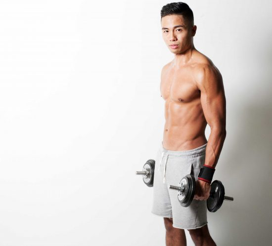 Artistic portrait of a fitness trainer on a white background.
