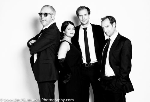 Artistic black and white portrait of a cast in formal wear.