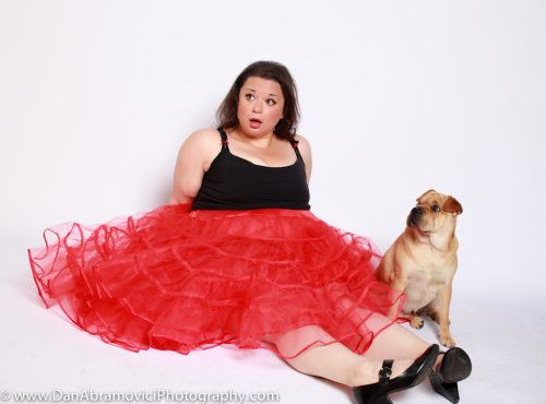 Artistic portrait of a woman in a red skirt with a dog on a white background.