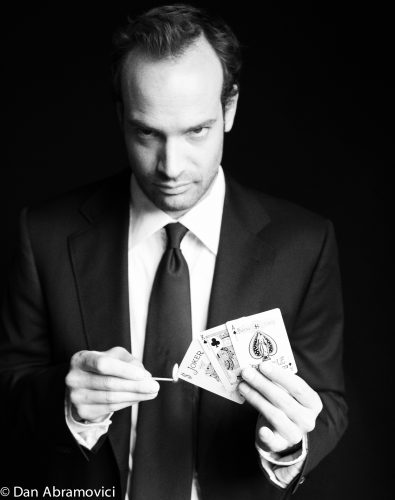 Artistic black and white headshot of an actor burning a handful of cards.