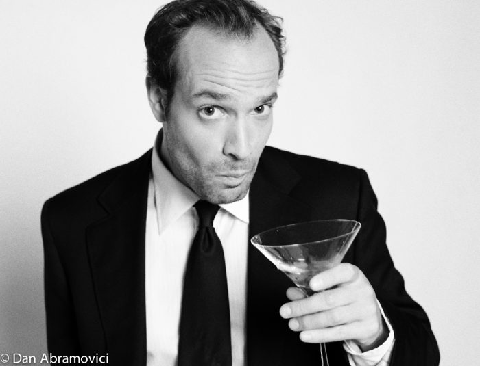 Artistic black and white headshot of an actor with a martini.