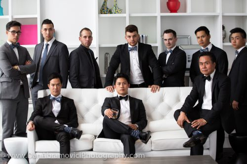 Professional wedding photo of a group of men in tuxedos and suits.