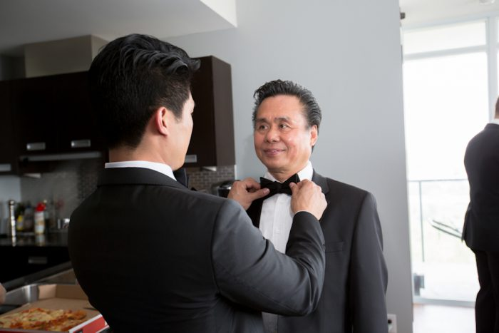 Beautiful wedding photograph of a son helping his father with his bow tie.