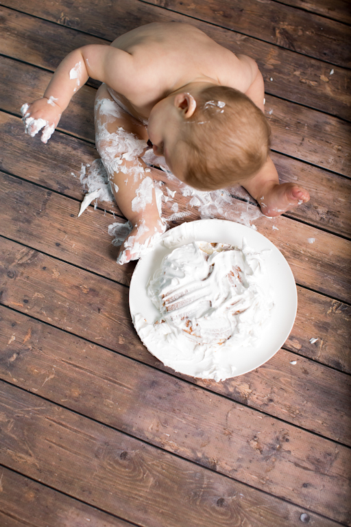 Artistic overhead portrait of a baby smashing a cake.