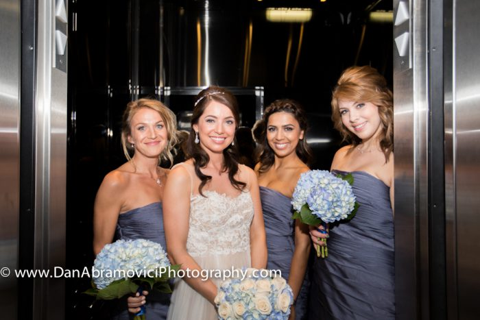 Professional portrait of a bride and her bridesmaids in a hallway ready for the wedding.
