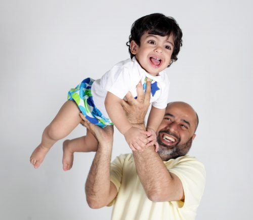 Professional portrait of a father and son against a white background.