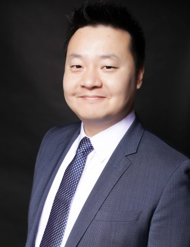 Professional business portrait of a man in a suit on a black background.