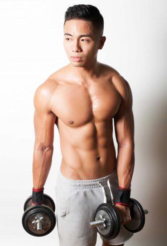 Professional portrait of bodybuilder with dumbbells.